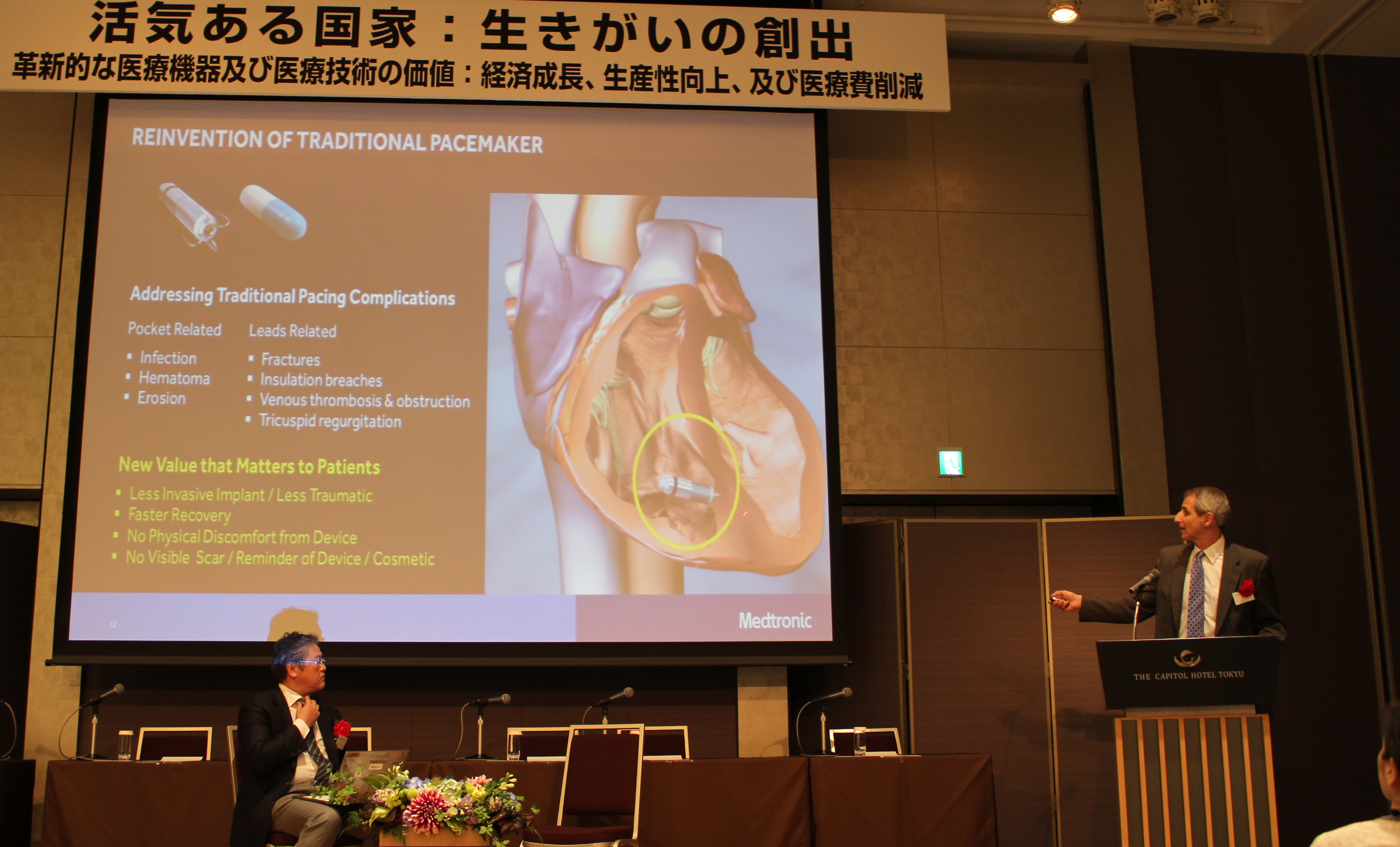 心臓ペースぺーカーの開発について話すロバート・コワル氏(壇上の左は池野文昭氏)